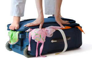 Barefooted woman standing on a suitcase crammed full of clothes, isolated, with clipping path